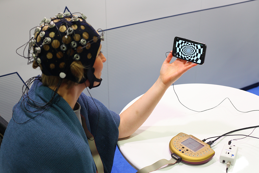 Photo Sensor (Neuroscience 2014): Visual-evoked potential demonstration at the SfN conference 2014 (Washington, USA). On a large cell phone display a reversing checkerboard pattern was shown. The Photo Sensor and StimTrak detected the stimulus onset. actiCAP Xpress electrodes and a V-Amp amplifier were acquiring EEG signal.